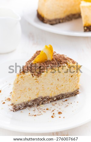 piece of orange cheesecake on a white plate, vertical, close-up - stock photo