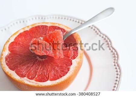 Piece of pink grapefruit in a tea-spoon, healthy citrus dessert - stock photo
