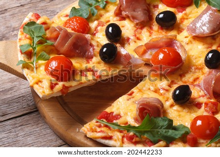 piece of pizza with ham, tomatoes, black olives and arugula closeup horizontal  - stock photo