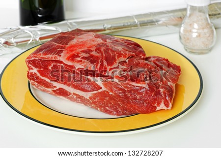 Piece of raw pork on a plate. Preparation for cooking - stock photo