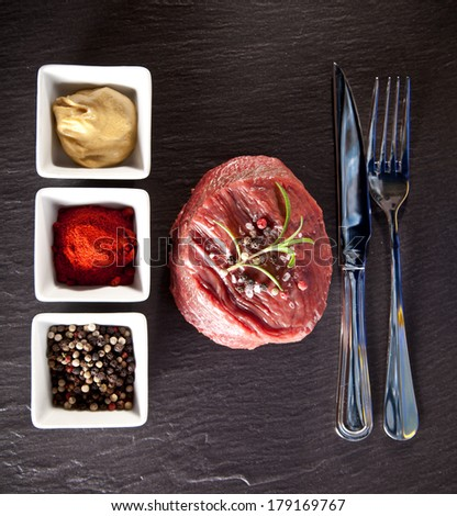 Piece of red raw meat steak with herbs, served on black stone surface. Shot from upper view. - stock photo