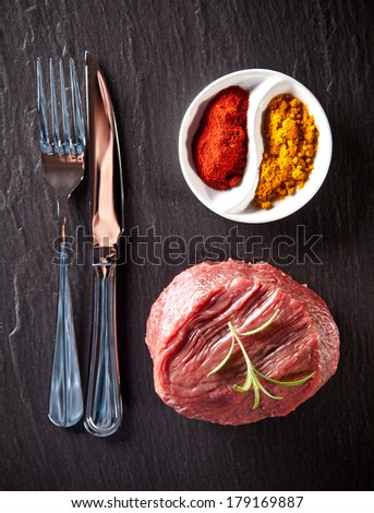 Piece of red raw meat steak with settings, served on black stone surface. - stock photo