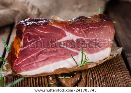 Piece of smoked Ham (with some fresh herbs) on wooden background - stock photo