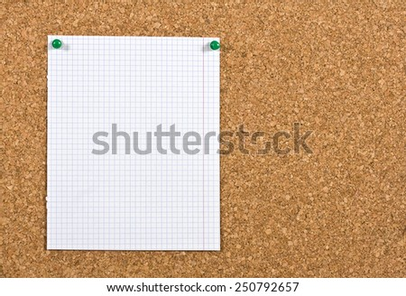 Piece of squared paper taken out of a notebook, the paper is pinned to a cork board, the photo is ideal as background for informations. - stock photo
