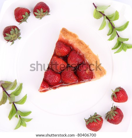 Piece of Strawberry Tart on white plate decorated with strawberries and mint twigs - stock photo