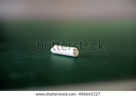 Piece of white chalk on blackboard - stock photo