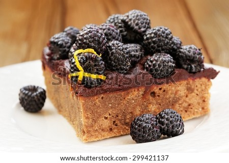 Piece of yummy chocolate pie with ganache, fresh blackberries and lemon peel decorated with icing sugar in white plate on wooden table - stock photo