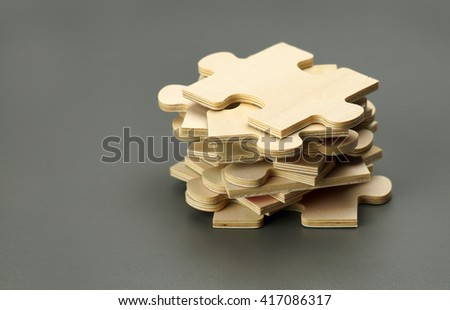pieces of a wooden puzzles isolated on dark background - stock photo