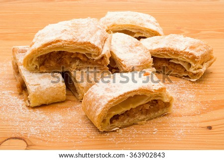 Pieces of apple pie on wooden table - stock photo
