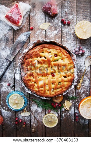 Pieces of apple pie sprinkled with powdered sugar. Homemade cut apple cake decorated slices of lemon and green spruce branches and pomegranate seeds on a wooden background. Rustic dark food style.  - stock photo