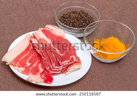 Pieces of bacon and spices - pepper pots and turmeric - stock photo