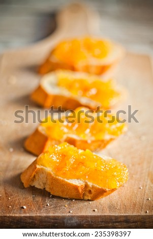 pieces of baguette with orange marmalade closeup wooden board - stock photo