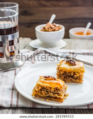 pieces of baklava with honey and nuts in a circular plate on a gray wooden background, rustic, traditional Turkish dessert - stock photo