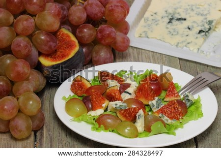 Pieces of blue cheese with figs and  grapes - stock photo