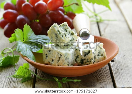 pieces of blue cheese with red grapes on a wooden table - stock photo