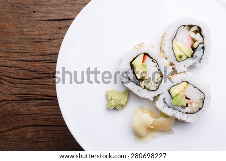 Pieces of California roll sushi on a white plate. - stock photo