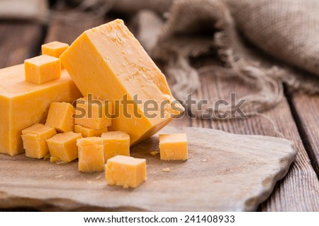 Pieces of Cheddar (close-up shot) on an old wooden table - stock photo