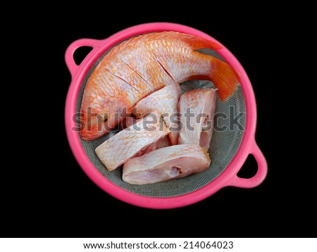pieces of chopped nile tilapia on a black background - stock photo
