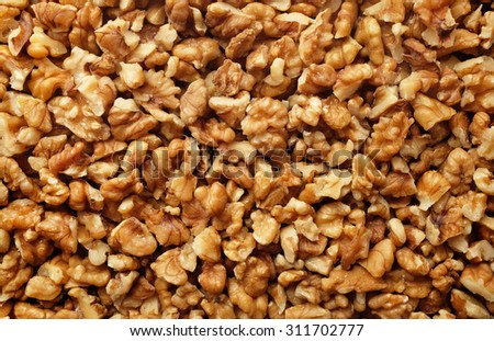 Pieces of chopped walnut as an abstract background texture - stock photo