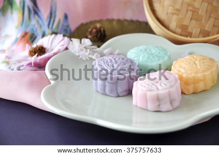 Pieces of colorful snow skin mooncake with pink flower on background - stock photo