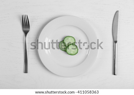 Pieces of cucumber in a white plate on white table. Top view. - stock photo