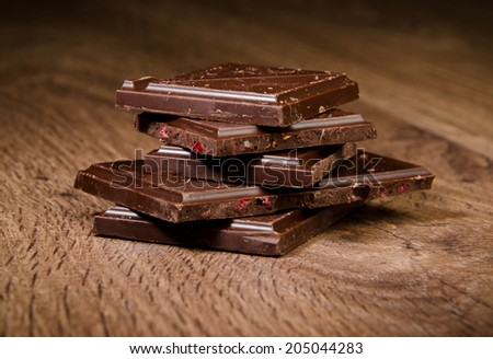 Pieces of dark chocolate on a wooden background - stock photo
