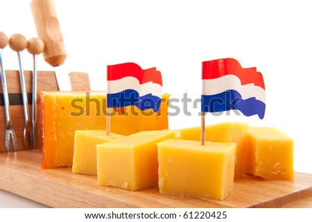 Pieces of Dutch cheese on timber board - stock photo