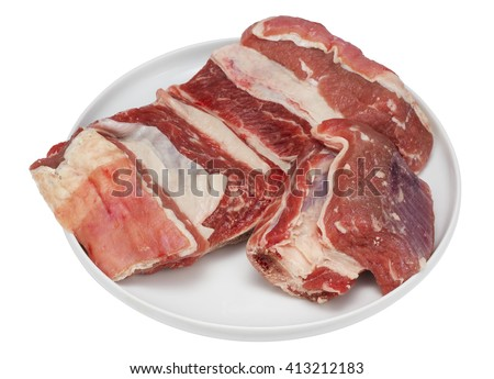 Pieces of fresh beef ribs with a bone and fat  on the round white ceramic plate. Cheap ingredient for tasty soup. Isolated with patch - stock photo