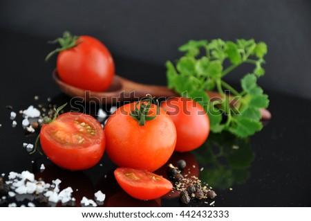 Pieces of fresh cherry tomato on black background - stock photo
