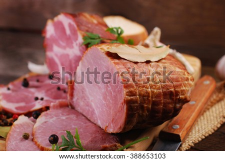 pieces of fresh homemade smoked ham with spices on rural background - stock photo