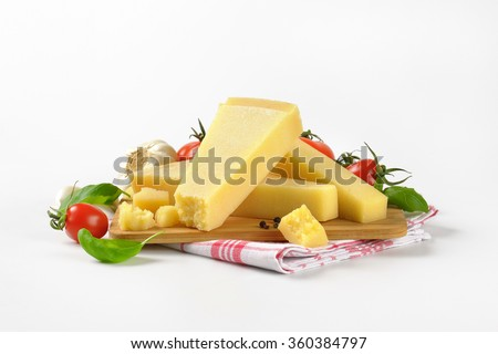 pieces of fresh parmesan cheese and vegetable garnish on wooden cutting board - stock photo