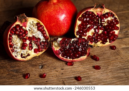 Pieces of fresh pomegranates on rustic wooden table - stock photo