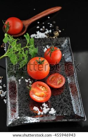 Pieces of fresh tomato on black tray - stock photo