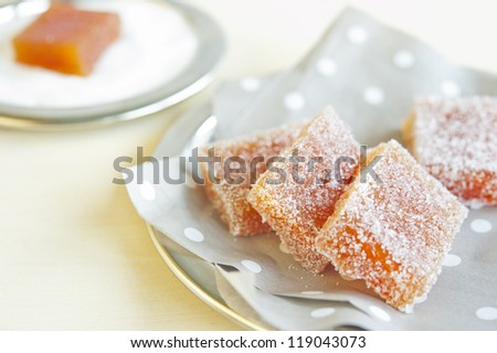 Pieces of fruit candy on a napkin in peas on a wooden table - stock photo