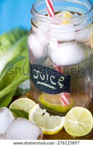 pieces of lime and lemon with lemon juice mug - stock photo