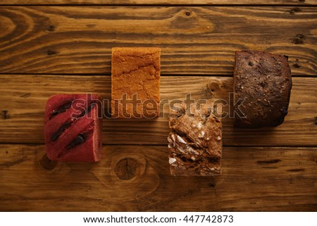 Pieces of mixed homemade breads presented in different levels on wooden table as samples for sale made from sweet potato, sea salt, rye and beetroot Top view - stock photo