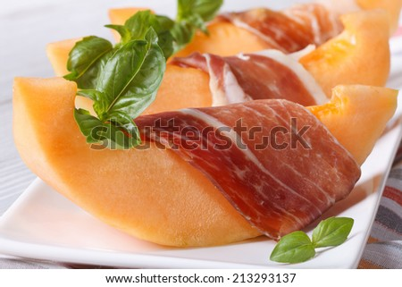 pieces of orange melon wrapped in prosciutto and basil on a white plate on the table. Horizontal close-up  - stock photo