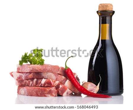 Pieces of pork meat with parsley and vinegar bottle - stock photo