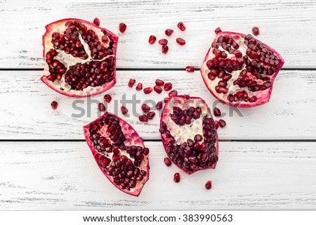 Pieces of ripe juicy pomegranate and pomegranate seeds on a white wooden plank background. - stock photo