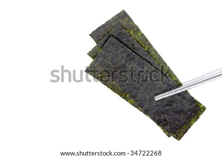 Pieces of seasoned dried seaweed held up with steel chopsticks, isolated on white with copyspace - stock photo