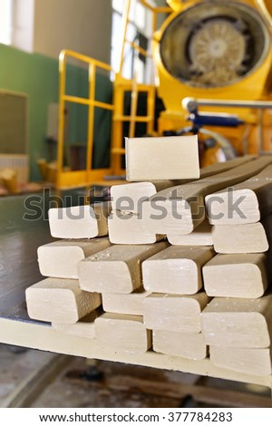 Pieces of soap on the assembly line at the plant for the production of soap - stock photo