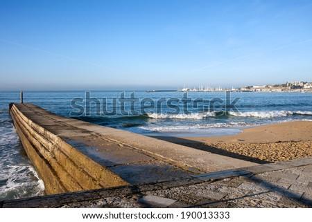 Pier and beach on the Atlantic Ocean coast in Cascais, Portugal. - stock photo
