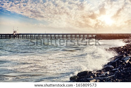 Pier and sea with waves at sunset sky background in Puducherry, India - stock photo