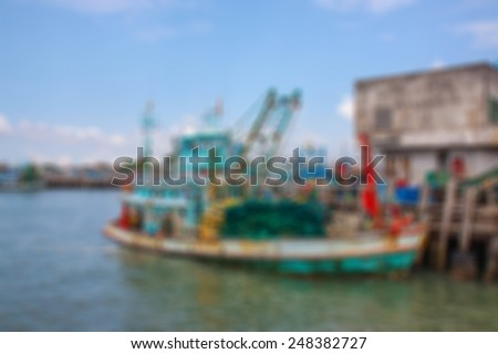 Pier fishing in the sea of Thailand. Has a large fishing boat blurred background. - stock photo