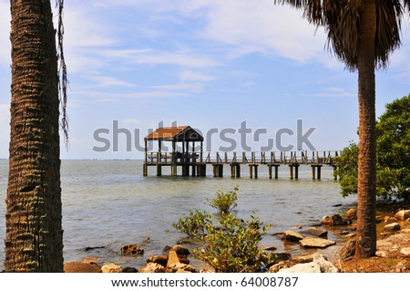 Pier leading to a pavillion where the bay comes to lap against the pillars in the water. This is a panoramic view of Tampa bay where trees and rocks line the waterfont and Boats are seen cruising by. - stock photo