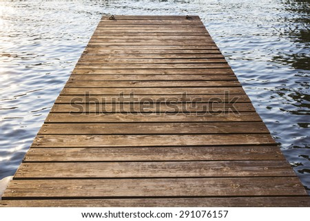 pier made of wooden boards on the river - stock photo