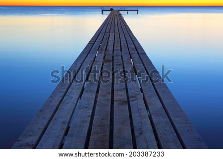 Pier on the sea during a calm - stock photo