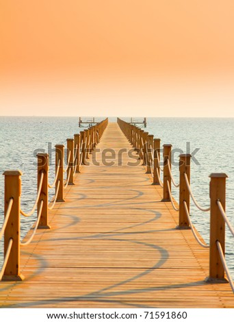 Pier over Sunset Waters - stock photo