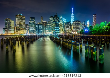 Pier pilings and the Manhattan skyline at night, seen from Brooklyn Bridge Park, New York. - stock photo