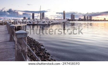 Pier with Boats and Yachts Reflecting in the Canal and Overlooking Southport During a Beautiful Sunset, Main Beach, Gold Coast, Queensland, Australia - stock photo